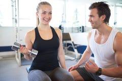 Gym trener Pomaga kobiety w udźwigów ciężarach obraz stock
