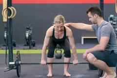 Gym trenera pomaga kobieta z podnośnym barbell obrazy stock