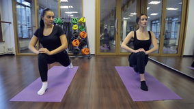 In gym two young women sitting down on a forward split on mats. stock video footage