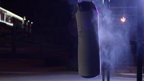 Gym, Uderza pięścią torby Uderzać pięścią torby w bokserskim pokoju, sport Uderzający pięścią torbę przy zmrok sportami mlejącymi Zdjęcie Stock