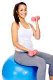 Gym woman on ball with dumbbells Stock Photography