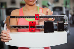Gym: Woman Checks Weight on Traditional Scale Royalty Free Stock Images