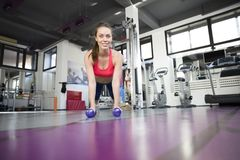 Gym woman doing pushup exercise with dumbbell in gym Royalty Free Stock Images