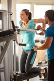 Gym,woman exercise muscles with assisting her personal trainer. Personal trainer working with his client in gym Royalty Free Stock Images