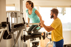 Gym,woman exercise muscles with assisting her personal trainer. Personal trainer working with his client in gym Stock Photos