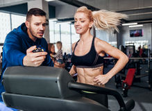Gym woman exercising with her personal trainer Royalty Free Stock Photography