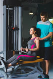 Gym woman and her trainer doing exercise at the gym Royalty Free Stock Photo