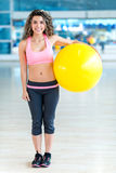 Gym woman holding a Pilates ball Stock Images