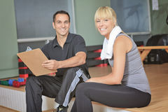 Gym woman personal trainer man with weight training equipment Stock Image