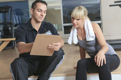 Gym woman personal trainer man with weight Stock Photo