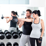 Gym woman personal trainer with weight training. Gym women personal trainer men with weight training equipment Royalty Free Stock Photography