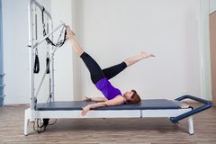Gym woman pilate instructor stretching in reformer Stock Image