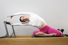 Gym woman pilates stretching sport in reformer bed Royalty Free Stock Photo