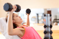 Gym woman strength training lifting weights. Gym woman strength training lifting dumbbell weights in shoulder press exercise. Female fitness girl exercising Stock Images
