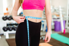 Gym woman taking measurements with a tape measure Royalty Free Stock Photo