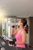 Gym woman working out drinking water by moonwalker fitness machi Stock Images
