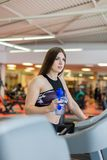 Gym woman working out drinking water smiling happy standing by moonwalker fitness machines. Beautiful fit young mixed stock images