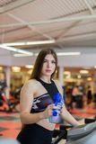 Gym woman working out drinking water smiling happy standing by moonwalker fitness machines. Beautiful fit young mixed royalty free stock image