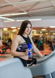 Gym woman working out drinking water smiling happy standing by moonwalker fitness machines. Beautiful fit young mixed royalty free stock images