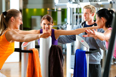 Gym - women and trainer front of exercising machin. Women and trainer in gym in front of a exercising machine doing fitness exercises Stock Photos