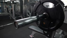 Gym worker adding weight plate barbell, checking equipment, high quality service. Stock footage stock footage