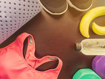 Gym workout accessory with pink sportswear , black footwear, yog. A mat and banana , bottle of cool water for support energy up with soft focus wood background Stock Images