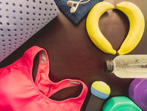 Gym workout accessory from pink sportswear , yoga mat , dumbbell. And refresh energy by banana and relax by listen music with earphones with soft focus wood Stock Photos