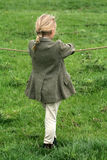 Gymkhana Girl. Little blonde girl with her hair plaited wearing jodphurs and riding jacket hangs onto the rope witing for her brother to get off her pony because royalty free stock image