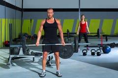 Gymnase avec l'homme et la femme de séance d'entraînement de bar d'haltérophilie Photo libre de droits