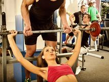 Gymnase de séance d'entraînement d'amis de forme physique Femme travaillant au banc à presse Image libre de droits