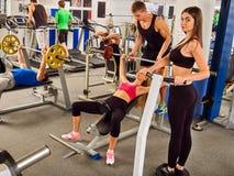 Gymnase de séance d'entraînement d'amis de forme physique Femme travaillant au banc à presse Image stock
