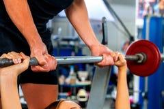 Gymnase de séance d'entraînement d'amis de forme physique Femme travaillant au banc à presse Photos stock