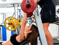 Gymnase de séance d'entraînement d'amis de forme physique Femme travaillant au banc à presse Photographie stock libre de droits