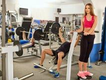 Gymnase de séance d'entraînement d'amis de forme physique Homme travaillant au banc à presse Images libres de droits