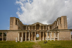 Gymnasium at Sardis in Turkey. Couple seated near of gymnasium ruins at Sardis in Turkey royalty free stock image