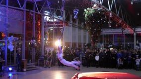 Gymnast γυναικών να κάνει παρουσιάζει στη στεφάνη αέρα μπροστά από το κόμμα ακροατηρίων τη νύχτα απόθεμα βίντεο