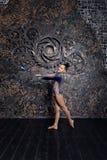 Gymnast κοριτσιών σε ένα μπλε κοστούμι με τα σπινθηρίσματα που κάνει την άσκηση με τις γυμναστικές λέσχες στοκ εικόνα