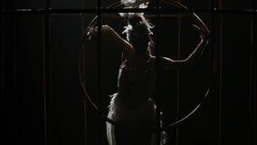 Gymnast που οδηγά μια στεφάνη σε ένα κλουβί στο σκοτεινό στάδιο Μαύρη ανασκόπηση κίνηση αργή κλείστε επάνω σκιαγραφία απόθεμα βίντεο