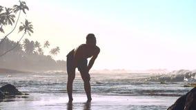 Gymnast στάσεις στα ρηχά νερά με τα χέρια στα γόνατα απόθεμα βίντεο