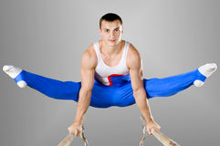 Gymnast. The sportsman the guy, carries out difficult exercise, sports gymnastics Royalty Free Stock Photos