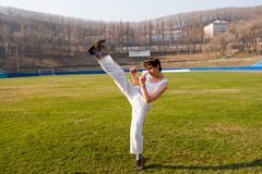 Gymnast. The young man does(makes) gymnastic exercises on a grass. Spring Royalty Free Stock Photo
