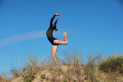 Gymnast arching her back on the beach Royalty Free Stock Image
