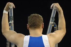 Gymnast bars 01. A male gymnast is about to preform a routine on the parallel bars during competition Stock Photos