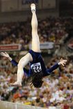 Gymnast beam 01. A female gymnast preforms a routine on the balance beam during competition Royalty Free Stock Photo