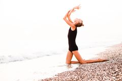 A gymnast in a beautiful pose against the background of the ocean. royalty free stock photos