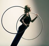 Gymnast in black skin-tight dress with two gymnastic hoops Stock Photography