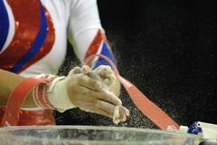 Gymnast chalk 001. A female gymnast chalks up her hands before performing during competition Royalty Free Stock Image
