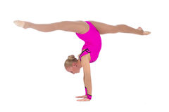 Gymnast in a costume doing stretching exercise. Smiling flexible girl gymnast in a costume doing stretching exercise over white background royalty free stock image