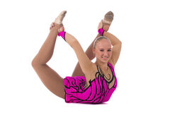 Gymnast in a costume doing stretching exercise. Smiling flexible girl gymnast in a costume doing stretching exercise over white background royalty free stock photos
