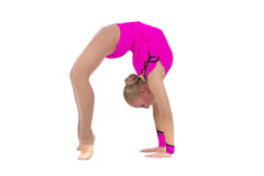 Gymnast in a costume doing stretching exercise. Smiling flexible girl gymnast in a costume doing stretching exercise over white background stock photography